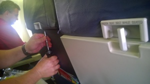 Southwest maintenance technician repairing the tray table latch.